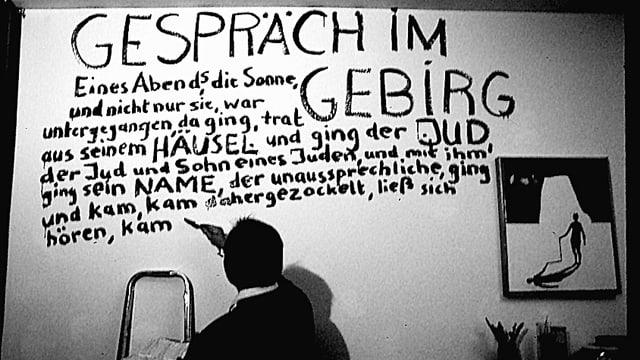 Ein Mann schreibt mit einem Pinsel einen Text an eine weisse Zimmerwand.