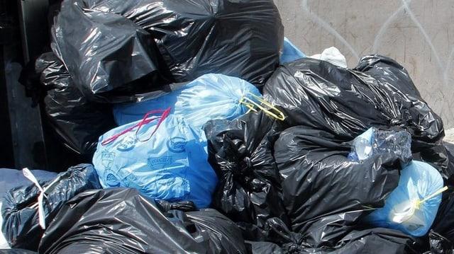 Blaue und Schwarze Abfallsäcke türmen sich.