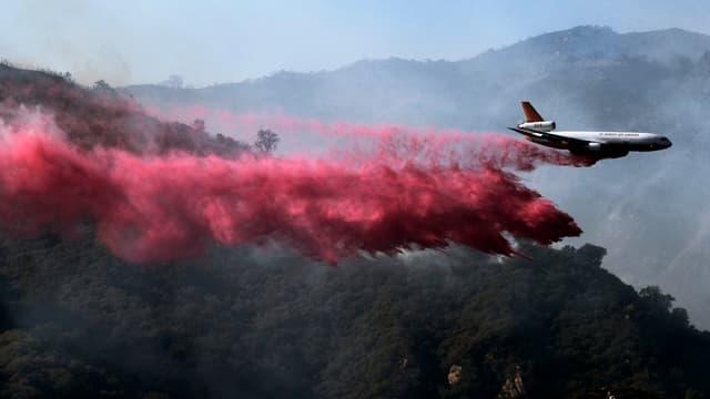 Löschflugzeuge werfen Feuer retardierendes Pulver über die Wälder ab.
