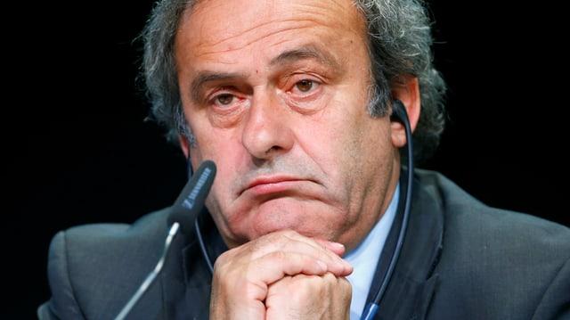 Platini sitzt vor einem Mikrofon, er macht ein wenig begeistertes Gesicht.