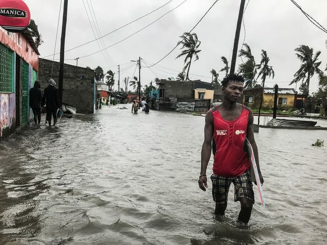 Ein Mann watet durch eine überschwemmte Strasse.