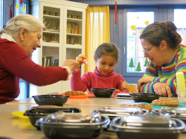 Eine Bewohnerin, ein Spielgruppenkind und die Spielgruppenleiterin beim Verzieren der Lebkuchen.