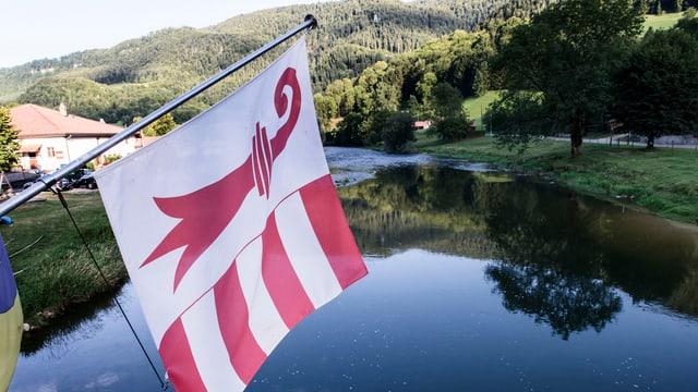 Eine Juraflagge, dahinter eine Jura-Landschaft