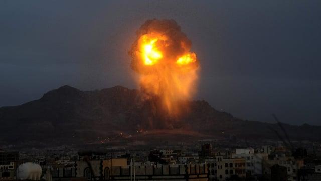 Eine riesige Feuerwolke steigt hinter der Stadt Sanaa auf