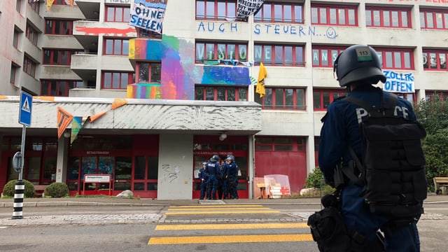 EIn Polizist steht vor dem besetzten Haus.