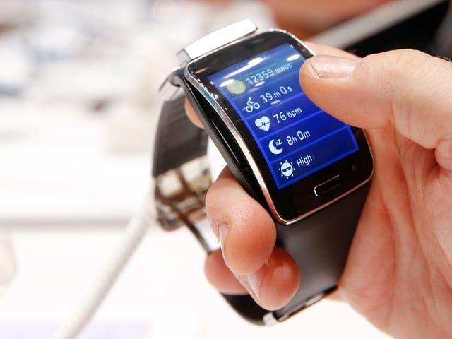 Eine Männerhand hält eine Gear S Smartwatch von Samsung.