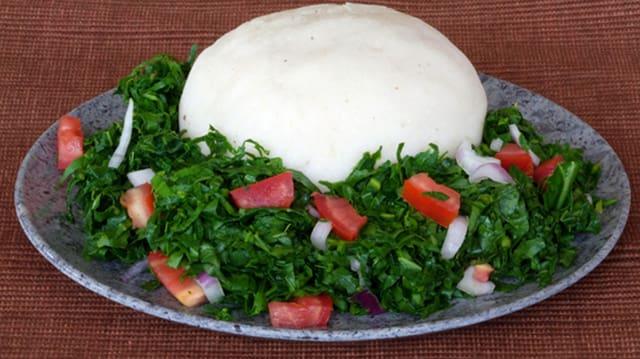 Auf einem Teller befindet sich weisser Ugali und grüner Spinat und Tomaten.
