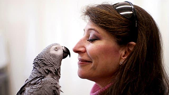 Eine Frau und ein Papagei schauen sich gegenseitig ins Gesicht.