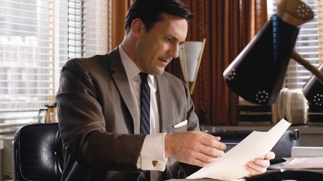 Don Draper (Jon Hamm) an seinem Bürotisch, in der Hand ein paar Papiere.