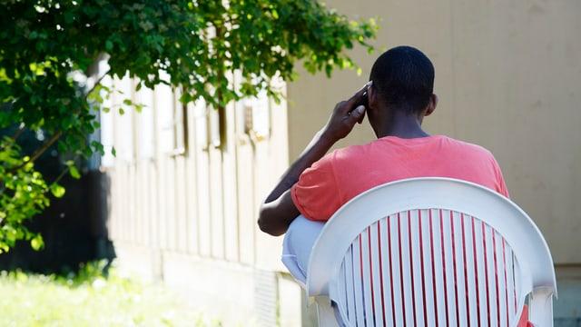 Asylbewerber telefoniert vor Baracke