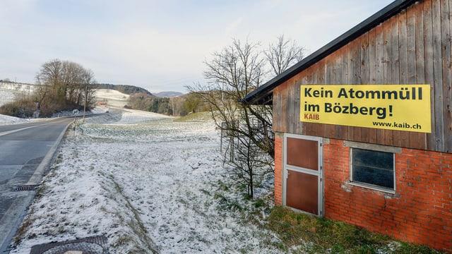 """Bauernhaus an Strasse, an der Hauswand ein Plakat mit der Aufschrift """"Kein Atommüll im Bözberg"""""""