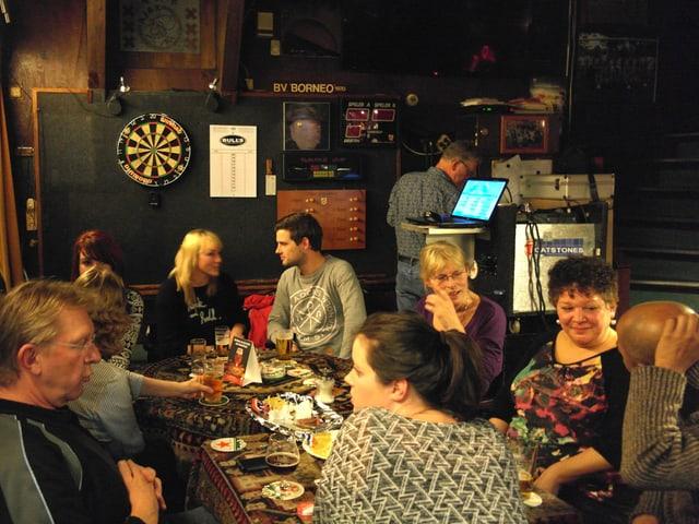 In der Kneipe sitzen die Stammgäste um den Tisch und trinken Bier.