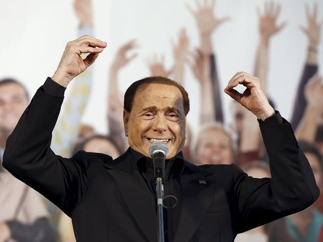 Silvio Berlusconi bei einer Rede - hinter ihm jubeln seine Anhänger.