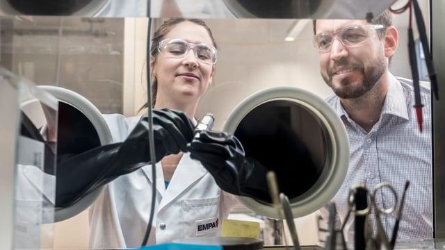 Zwei Wissenschaftler vor einem Glaskasten, die Frau hält mit Handschuhen ein Röhrchen.