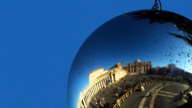 Eine Weihnachtskugel. Darin ist der Vatikan reflektiert.