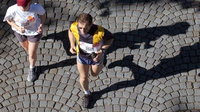 Zwei Menschen joggen, von oben aufgenommen.