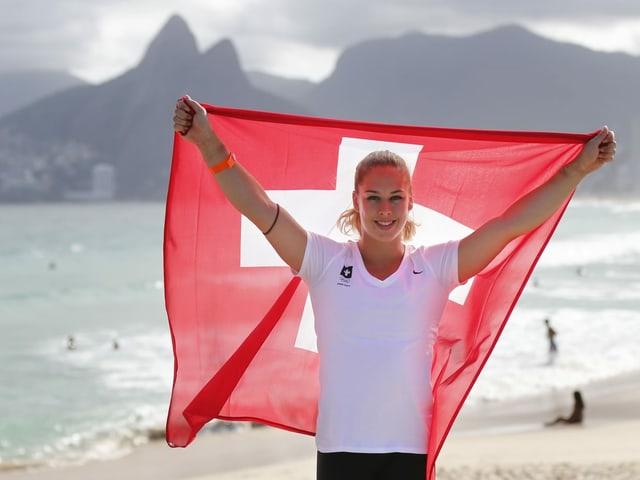 Giulia Steingruber posiert 2016 mit der Schweizer Fahne am Strand von Rio de Janeiro.