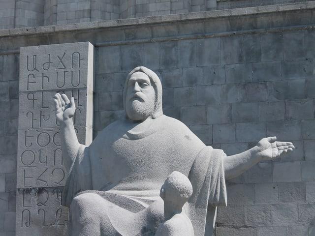 Steinstatue mit Schrifttafel.