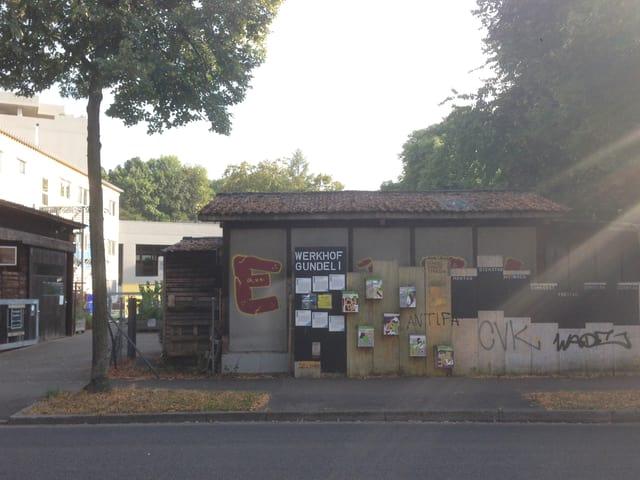 Ein Baum und ein Schild auf dem Werkhof steht