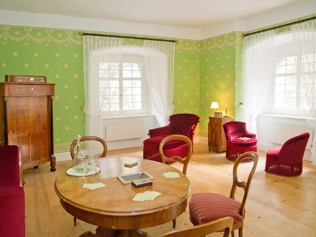 Grosszügiges historisches Gästezimmer mit Sitzgelegenheiten, Holztisch und Schrank.