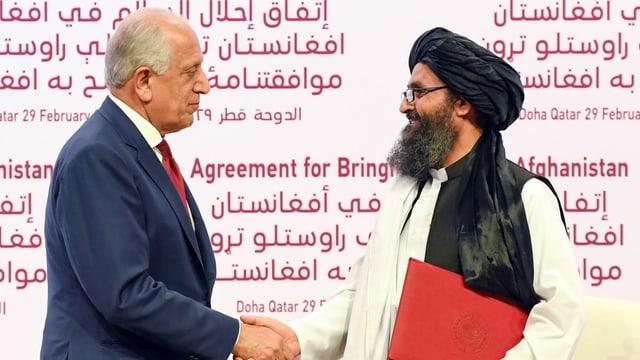 US-Verhandlungsführer Zalmay Khalilzad (l.) mit dem Vertreter der Taliban, Mullah Abdul Ghani Baradar.