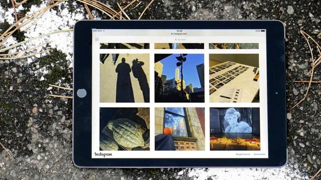 Ein Tablet liegt auf der Strasse. Darauf sind Fotos mit verschiedenen Motiven zu sehen.