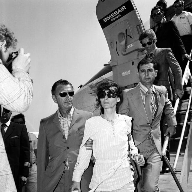 Eine dünne Frau mit Sonnenbrille steigt aus einem Flugzeug und wird links und rechts von Männern festgehalten.