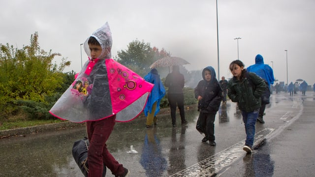 Kinder laufen im strömenden Regen auf einer Strasse,