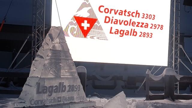 Il logo cuminaivel da las regiuns Corvatsch, Diavolezza e Lagalb, a sinistra la sculptura da glatsch