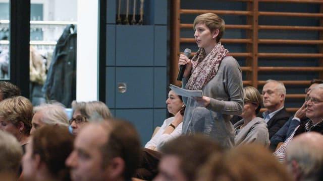 Eine junge Frau steht mit einem Mikrofon bei einer Versammlung zwischen sitzenden Menschen.