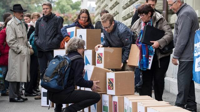 Leute mit vielen Kartons die mit den Kantonswappen gekennzeichnet sind, stehen vor dem Bundeshaus.