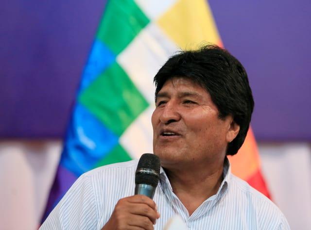 Evo Morales spricht in eine Mikrofon, das er in der Hand hält.