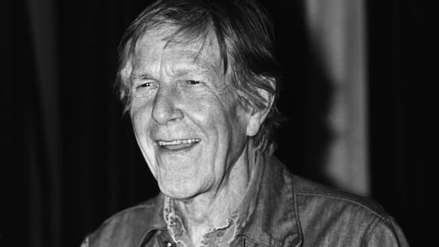 Schwarz-weisse Portraitaufnahme von einem lachenden John Cage.