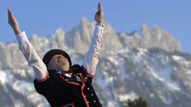 Ein Mann in Tracht hält die Hände zum Himmel und schaut hoch.
