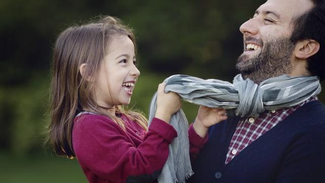 Ein Mann und ein Kind lachen schallend.