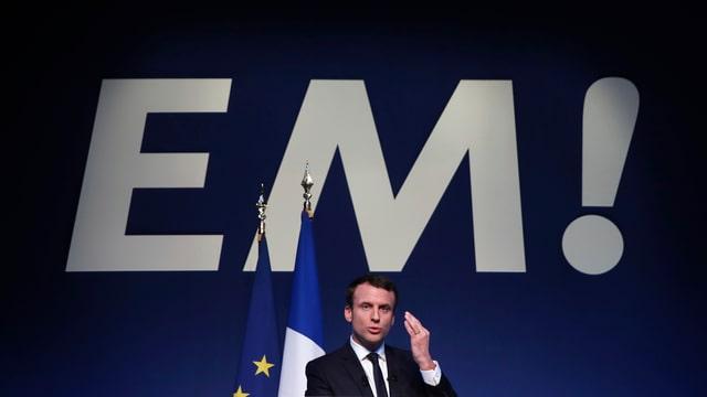 Macron spüricht, dahinter Frankreich- und EU-Flagge sowie in Grossbuchstaben «EM!».