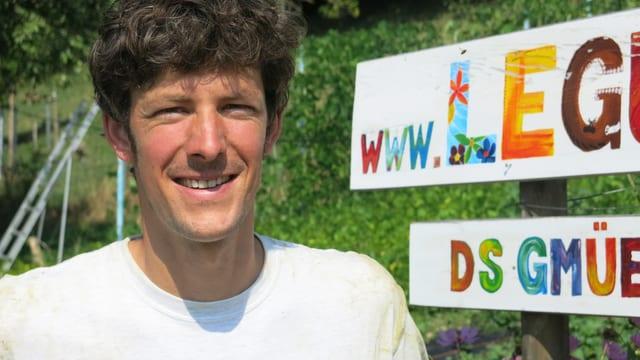 Porträt von Daniel Flühmann vor seinem Gemüsegarten.