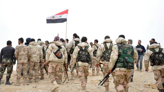 Schuldads sirians van cun la bandiera siriana vers la citad da Palmyra