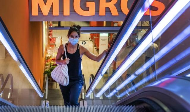 Frau auf Rolltreppe mit Maske in der Migros