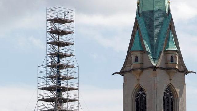 Ein Kirchturm, daneben ein eingerüsteter Kirchturm.