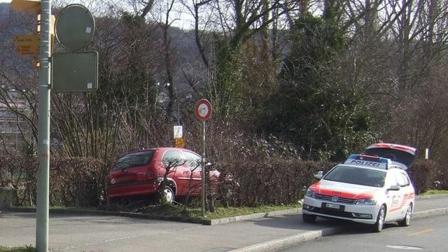 Das Unfallauto im Gebüsch, daneben ein Polizeiauto.