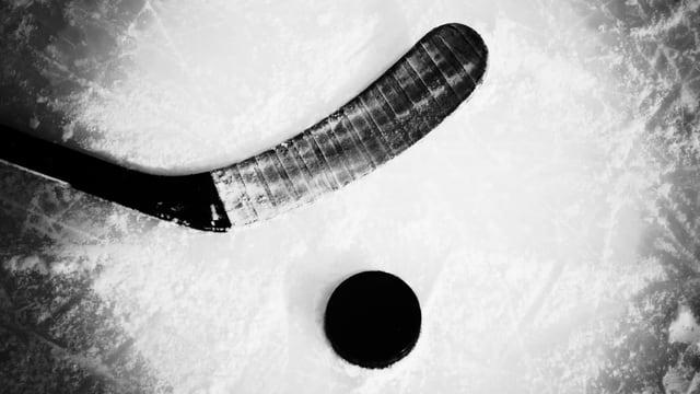Eiskhockeyschläger auf Eis, daneben Puck.