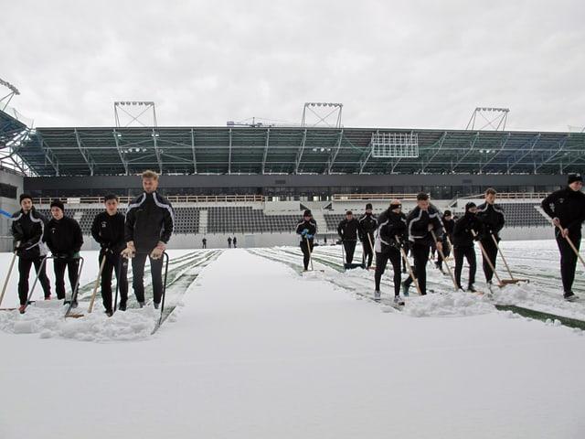 Eine Gruppe junge Männer räumen den Schnee von einem Spielfeld.
