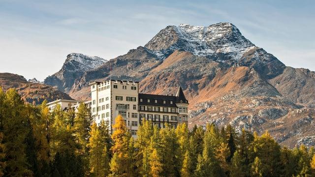 Das Waldhaus. Ein altes Hotel im Wald unter einem Berg. Es ist Herbst und die Nadelbäume sind gelblich gefärbt.