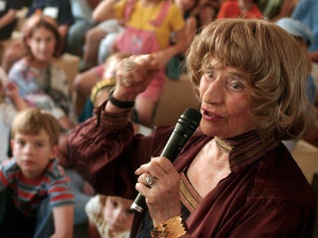 Ältere Dame mit Mikrofon erzählt Geschichten. Kinder hören ihr aufmerksam zu.