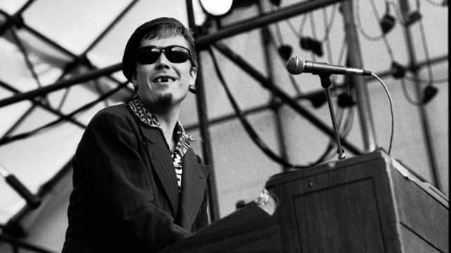 Jerry Dammers am Piano auf der Bühne. Er hat kaum Zähne.