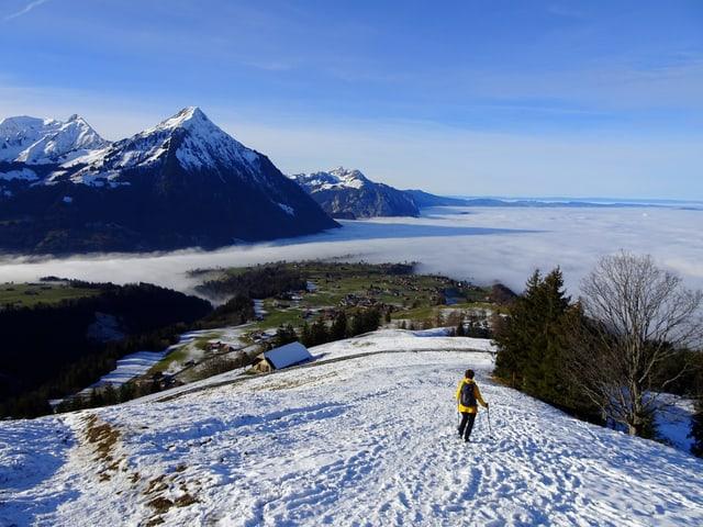 Ein Wanderer im Schnee blick hinunter auf die Hochnebeldecke. Im Hintergund hohe Bergipfel, am Himmel sind dünne Wolkenschleier vorhanden.
