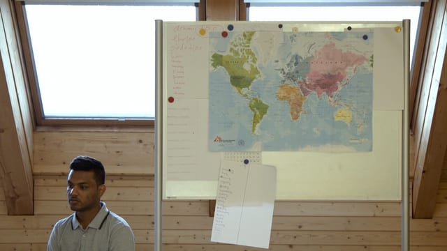 Tarjan sitzt neben einer Landkarte.