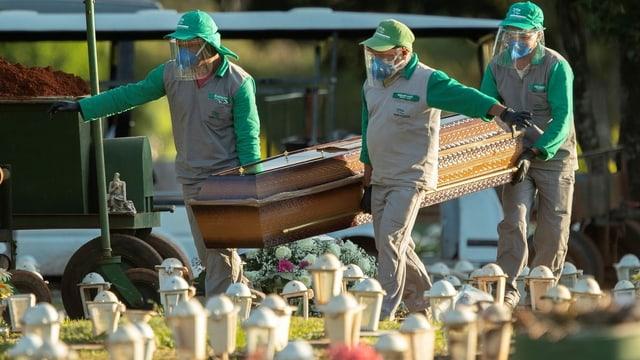 Drei Menschen tragen einen Sarg auf den Friedhof.
