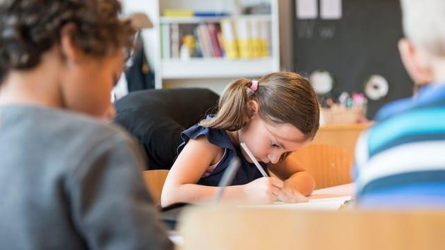 Ein Schulkind am Pult beim Schreiben.